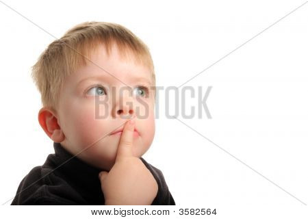 Cute Young Boy With Blonde Hair Looking Up With Finger On Lips