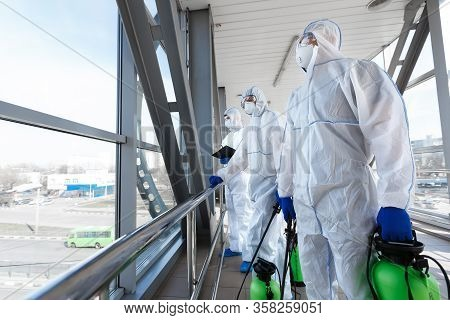 Medical Workers In Hazmat Suits Disinfecting With Spray Public Places From Coronavirus Cells Epidemi
