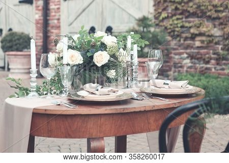 Candles And Vase With White Roses Placed On Round Table Near Wineglasses During Romantic Date In Gar