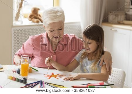 Family Leisure Activities. Cute Kid With Granny Painting With Gouache At Table In Kitchen
