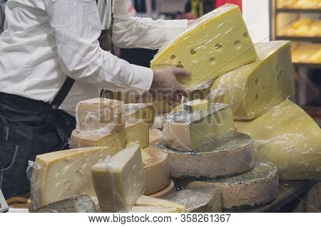 Man Salesman In The Shop With  Cheese. Food