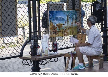 Kiev, Ukraine - July 28, 2019: Artist Paints Picture On Andreevsky Descent Street