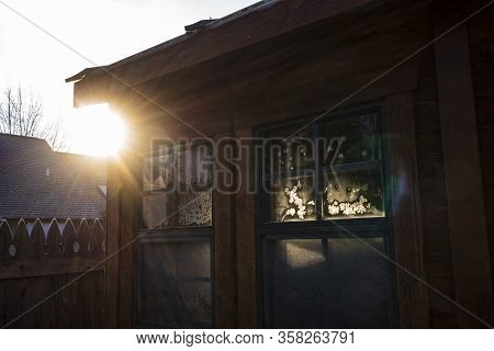 Sunrays Illuminate A Frost Pattern On A Window Of A Cedar Tool Shed On A Winter Morning.