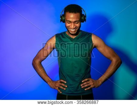 Fitness Workout. Athlete Man In Fitwear And Earphones Standing On Blue Studio Background. Neon Light