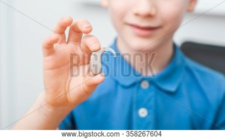 Advertising Hearing Aid For Children, A Caucasian Boy Showing A Hearing Aid. Childrens Hearing Treat