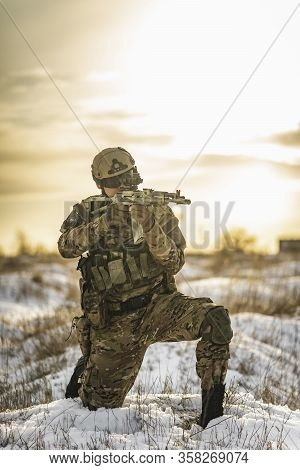 Equipped Army Soldier Man In The Winter Multicam Camouflage Is Patrolling Or Patrol Field Territory.