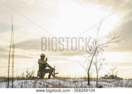 Modern War Soldier Army Man In Camouflage Speaks On The Walkie-talkie Radio Crouching On One Leg In