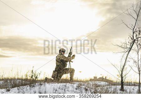 Modern War Soldier Army Man In The Winter Desert Put Gun On The Ground And Knelt Down. Full Equipmen