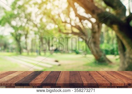 Empty Wood Table And Defocused Bokeh And Blur Background Of Garden Trees In Sunlight. Display Montag