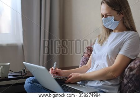 Young Woman In Medical Mask Works From Home During Self Isolation And Quarantine. Work Online And St