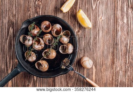 Bourgogne Escargot Snails With Herbs Butter In Iron Pan On Rustic Wooden Background. Top View