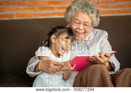 Closeup Photo Of Grandmother Teaches To Read A Book Her Granddaughter,family Concept.