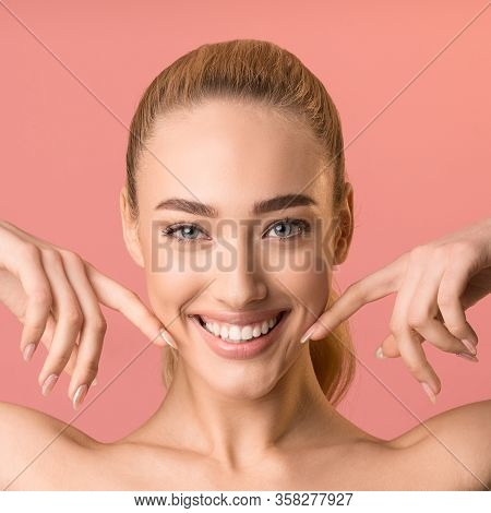 Perfect Smile. Happy Blonde Woman Smiling To Camera Touching Face Posing Over Pink Background. Studi
