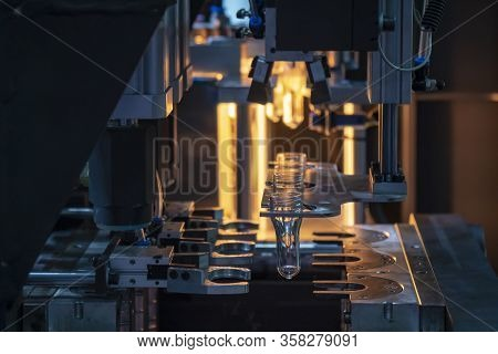 The Tube Preform Shape Of Bottles Preheat Process On The Production Line To The Automatic Blowing Ma