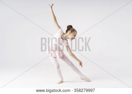 Delicate Girl Ballerina Standing In Ballet Pose On White Background In Studio. Kinds Personality Dev