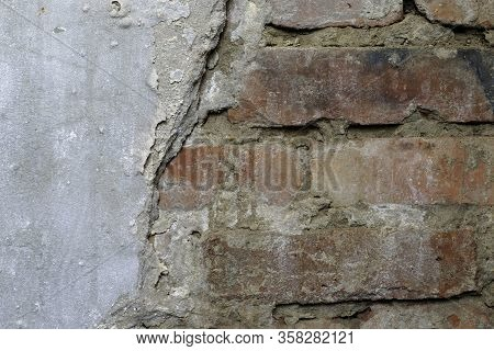 Part Of The Wall With Crumbling Plaster From Under Which A Red Brick Is Visible For A Backdrop Backg
