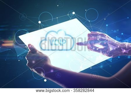 Hand holdig futuristic tablet with VOIP inscription, modern technology concept