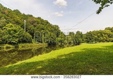 Weisse Elster River With Trees Mirroring On Water Ground, Forest And Meadow Around And Blue Sky With