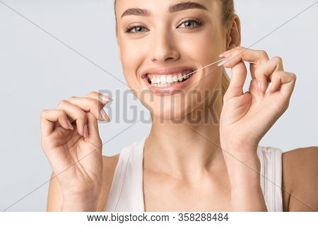 Teeth Flossing. Smiling Girl Using Floss Cleaning Teeth Doing Oral Hygiene Routine Standing Over Gra