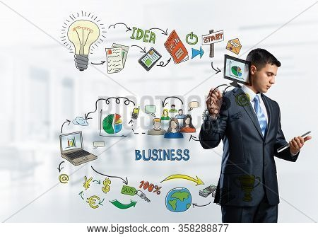 Handsome Businessman Standing And Pointing At Business Doodles. Front View Of Man In Business Suit A