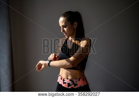 Sporty And Active Lifestyle. A Young Woman In A Sporty Cropped Top And Leggings Looks At A Fitness B
