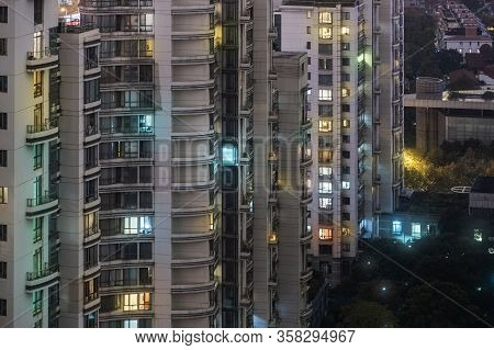 Closeup View Of Highrise At Night Time. Colorful Illuminated Windows. Residential Buildings And Gard