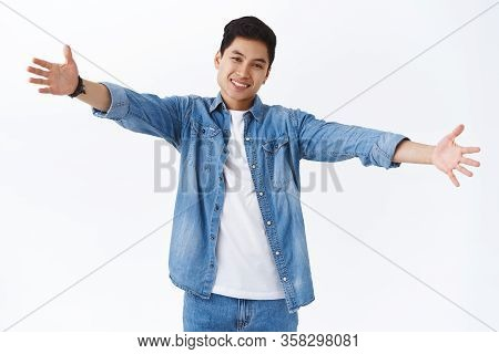 Portrait Of Friendly Charismatic Young Handsome Taiwanese Man Reaching You For Tight Warm Hug, Stret