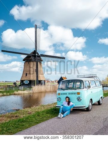 Alkmaar Netherlands April 2019, Classic Old Vintage Car Van Parked By Historical Windmill In Holland