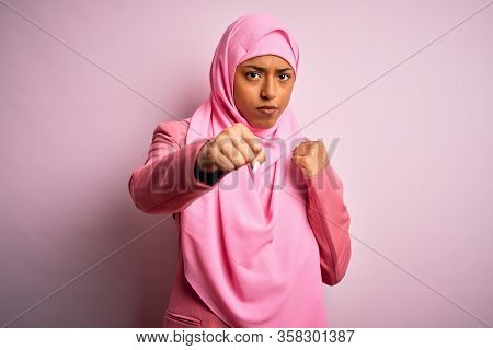 Young African American afro woman wearing muslim hijab over isolated pink background Punching fist to fight, aggressive and angry attack, threat and violence