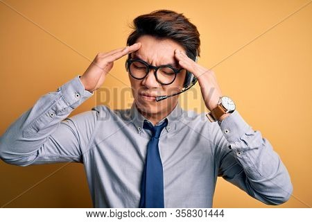 Young handsome chinese call center agent man wering glasses using headset suffering from headache desperate and stressed because pain and migraine. Hands on head.