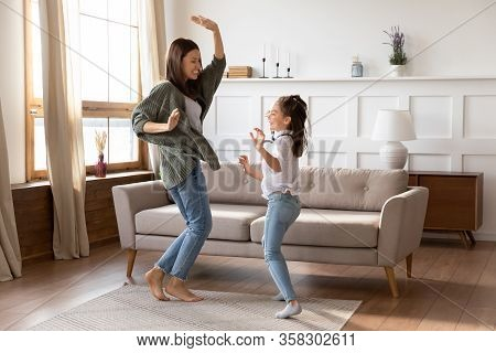 Overjoyed Young Mommy Babysitter Dancing To Music With Girl.