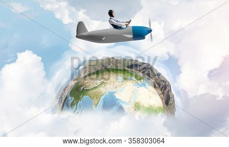 Happy Pilot Driving Small Propeller Plane On Background Of Blue Sky With Clouds. Traveling Around Th