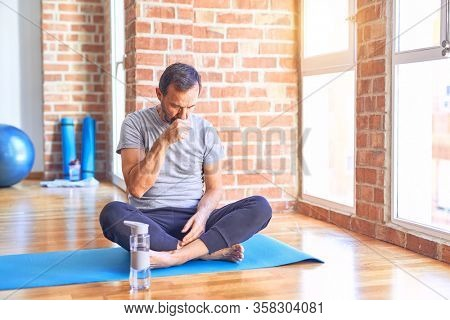 Middle age handsome sportman sitting on mat doing stretching yoga exercise at gym feeling unwell and coughing as symptom for cold or bronchitis. Healthcare concept.