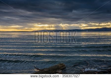 Rays Of Sunligh Break Through Dark Clouds Over The Puget Sound In Washington State.