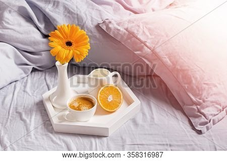 Tray With Coffee, Ornage And Flower Standing On The Bed