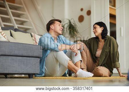 Warm Toned Full Length Portrait Of Modern Young Couple Talking To Each Other Sincerely While Sitting