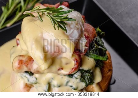 Eggs Benedict Or Eggs Florentine On A Black Plate In The Cafe. Egg Benedict On Toasted English Muffi