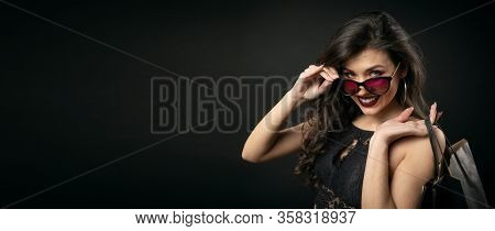 Glad Brunette Holding Shopping Bags On Shoulder Looking Camera Over Sunglasses, Black Copyspace