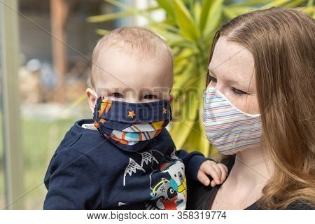 Portrait Of Baby And Mother Together With Reusable Protective Homemade Face Mask. Baby Boy Is Lookin