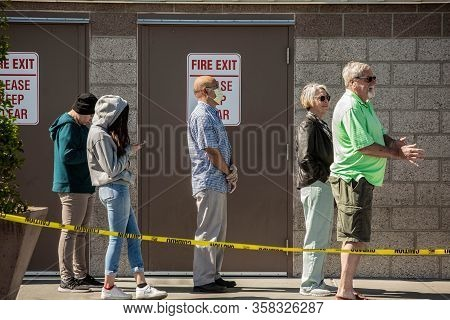 Tucson, United States  - March 29: Shoppers Practicing Social Distancing Lined Up Outside Retail War