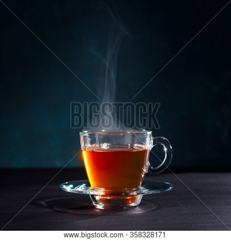 Freshly Brewed Black Tea In A Transparent Glass Cup, Escaping Steam, Darker Background.