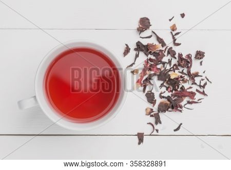 Red Tea In White Cup.the Brewing Process, Dry Tea Leaves, White Background.the View From The Top.
