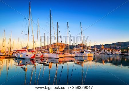 Trogir Cityscape With Sailing Boats In The Harbor At Dawn. Beautiful Travel And Touristic Destinatio