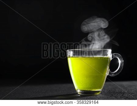 Freshly Brewed Green Tea In A Transparent Glass Cup And Teapot, Escaping Steam, Darker Background.