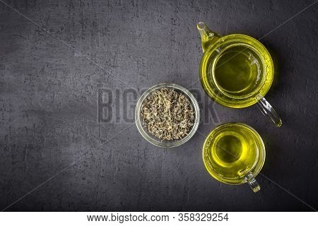 Green Tea, Brewed In A Transparent Teapot.dry Tea Leaves, Dark Black Background.the View From The To