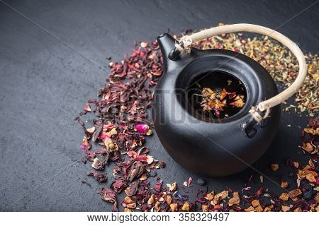 Black Ceramic Teapot With Tea, Different Tea On Dark Concrete Background.