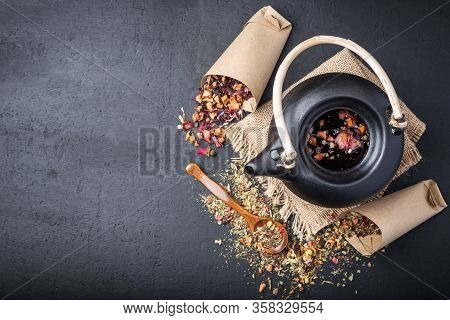Black Ceramic Teapot With Tea, Different Tea And Herbs , Dried Rose Flowers On Dark Concrete Backgro