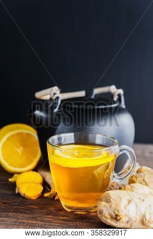 Healing Tea With Ginger And Lemon . Transparent Cup With Black Teapot On Wooden Background.