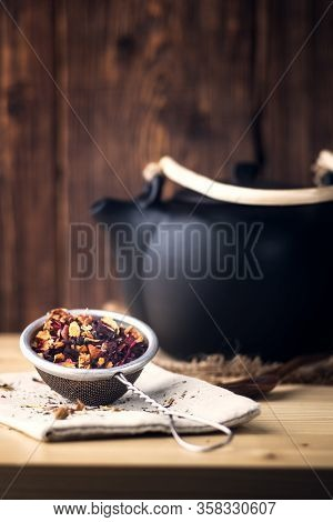 Black Ceramic Teapot With Tea, Tea In A Metal Sieve , On Wooden Background.