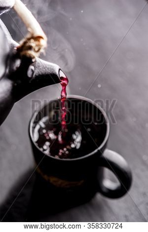 Process Brewing Tea, Cup Of Freshly Red Tea, Dark Mood.hot Water Is Poured From The Kettle Into A Cu
